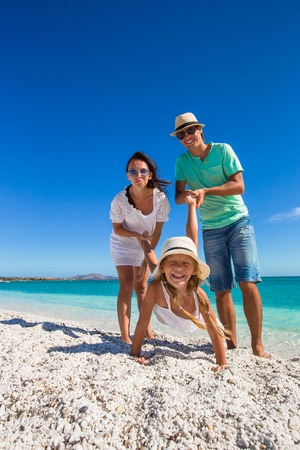 Young beautiful family of three have fun on tropical vacation photo