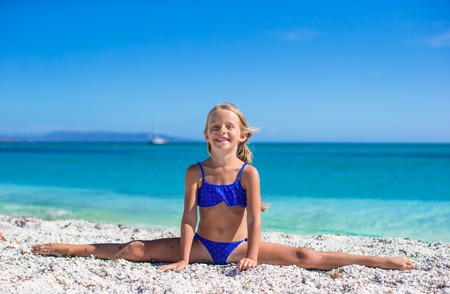 Adorable little girl making leg-split on tropical white sandy beach and enjoying summer vacation photo