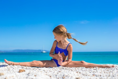 Adorable little girl making leg-split on tropical white sandy beach photo