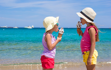 ice cream woman: Little happy girls eating ice cream on tropical beach