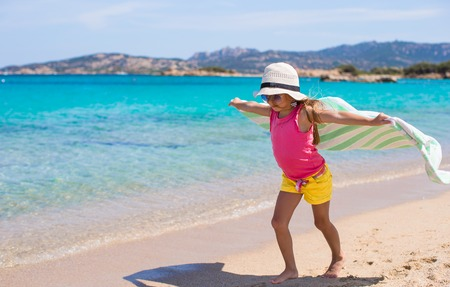 Little pretty girl running along the beach with towel and very happy photo