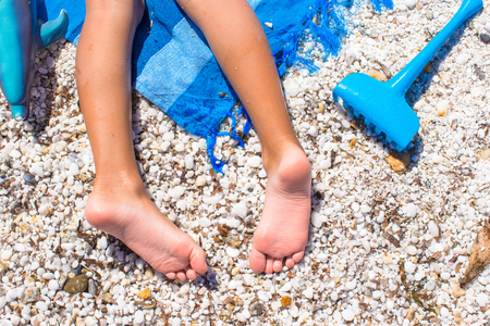 wet: Closeup of little girl legs on tropical beach with pebbles