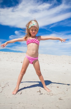 Adorable little girl in beautiful swimsuit have fun at tropical beach photo