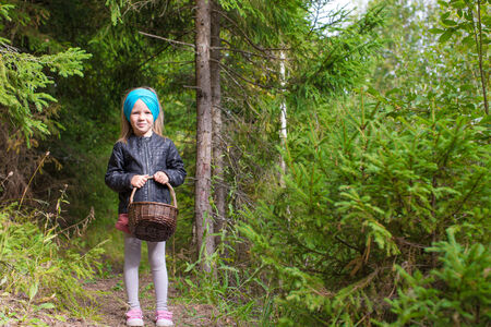 Little happy girl pick up mushrooms in autumn forest photo