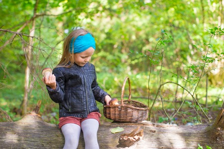 Little girl gathering mushrooms in an autumn forest photo