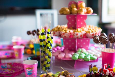 Canape van fruit, witte chocolade cake pops en popcorn op tafel zoete kinderen op verjaardagsfeestje