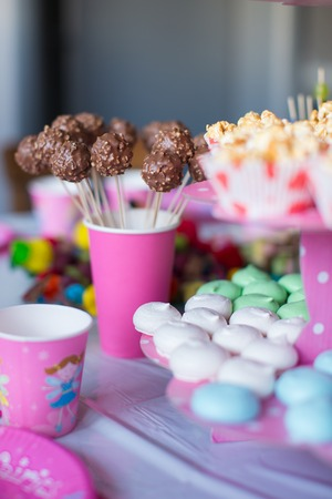 Sweet colored meringues, popcorn, custard cakes and cake pops on table photo