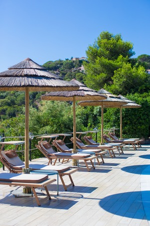 Wooden deck chairs and umbrellas near infinity pool in luxury resort photo