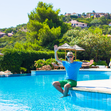 Happy man relaxing by swimming pool photo