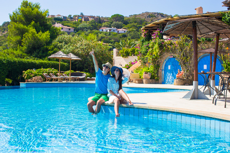 Lovely young romantic couple relaxing by swimming pool photo