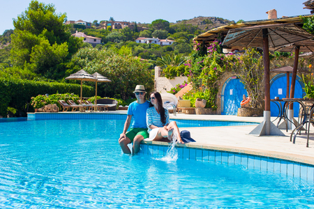 Young romantic couple near swimming pool at exotic resort photo