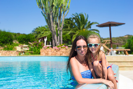 Mother and little girl relaxing in the quiet swimming pool photo
