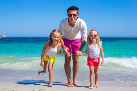 Young father and little girls have fun together during tropical vacation photo