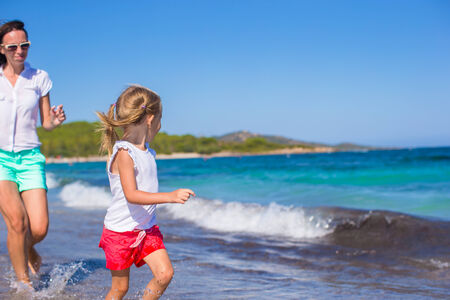 Young mother and little girl have fun together during tropical vacation photo