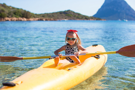rowing boat: Little happy cute girl enjoy kayaking in the clear blue sea Stock Photo