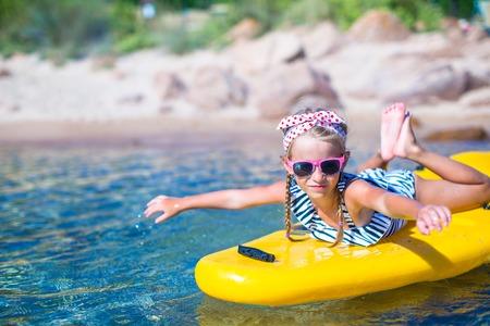 Little beautiful cute girl kayaking in the clear blue sea photo