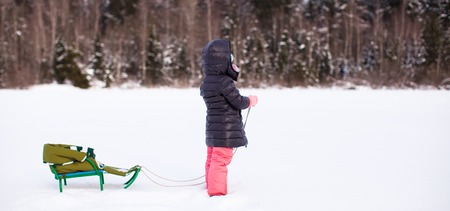 Little cute girl go sledding on a warm winter day photo