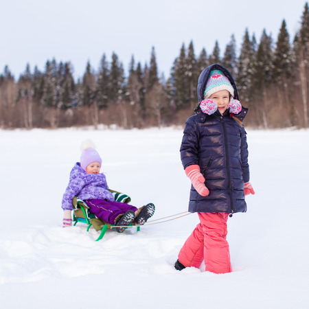 Adorable little happy girl sledding her cute sister photo