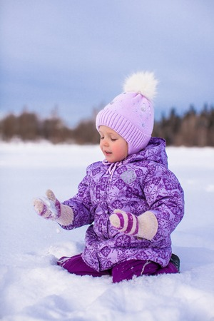 Little happy girl having fun on the snow at winter sunny day photo
