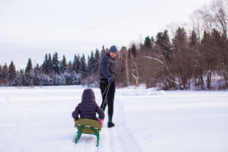 to go sledding: Young dad rolls his child on sledge in winter sunny day
