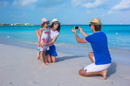 Young father making photo on phone of family at beach photo