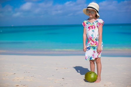 Adorable little girl with coconut at white beach have fun photo