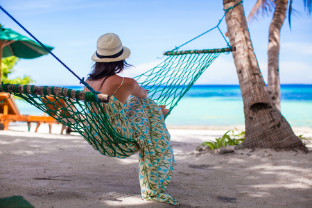 Young woman lying in the hammock on tropical beach photo