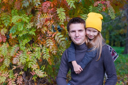 Adorable girl with happy father having fun in autumn park on a sunny day photo