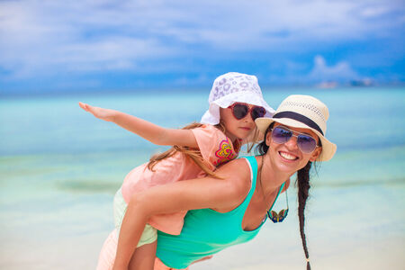 young family: Young mother and her adorable little daughter have fun at tropical beach