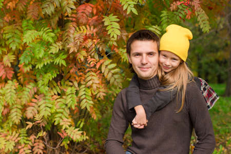 Adorable little girl with happy father having fun in autumn park on a sunny day photo