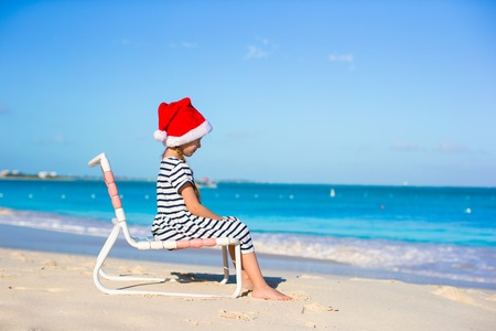 Little adorable girl in red Santa Hat on beach chair photo