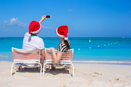 Family in red Santa Hat on beach chair photo