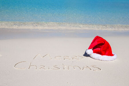 Merry Christmas written on tropical beach white sand with xmas hat photo