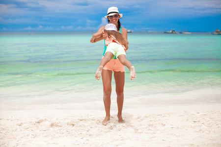 Young mother and little daughter have fun at tropical beach photo