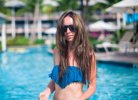 Young beautiful woman enjoying vacation in the pool photo