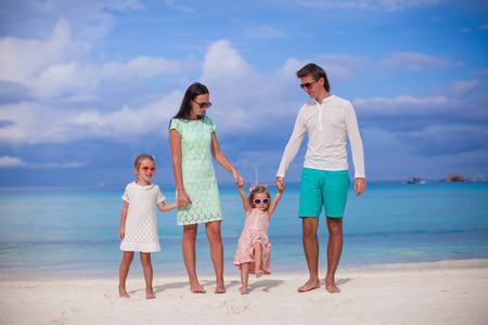 Family of four walking by the sea and enjoy beach vacation photo