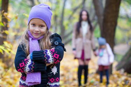 Little girls and young mother in autumn park outdoors photo
