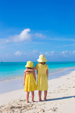 youngbaby: Back view of two little girls during tropical beach