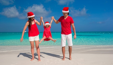 Happy family of three in Christmas Hats having fun on white beach photo