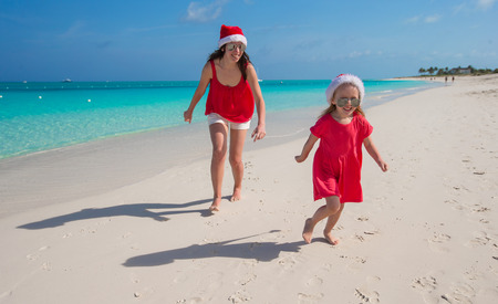 Mother and daughter having fun at tropical beach photo