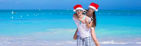 Young romantic couple in Santa hats during beach vacation photo