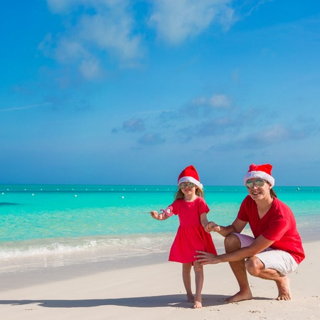 Little girl and happy dad in Santa Hat at exotic beach photo