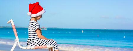 Little adorable girl wearing Santa hat at caribbean beach photo