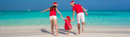 Happy family in Christmas Hats having fun on white beach Stock Photo