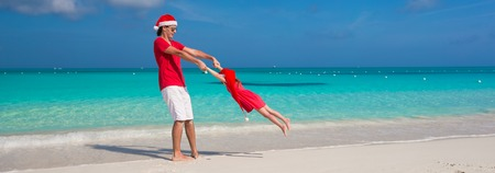 Little girl and happy dad in Santa Hat have fun at tropical beach photo