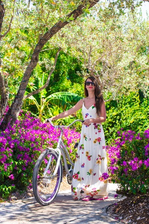 cycleway: Young woman on vacation biking at flowering garden