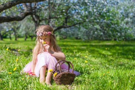 Cute little girl in blossoming apple garden at sunny spring day photo