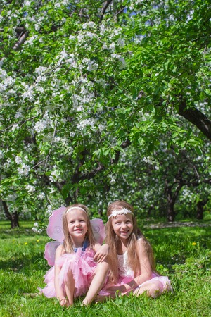 Little cute girls in the blossoming apple garden photo