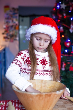 Adorable little girl baking gingerbread cookies for Christmas photo