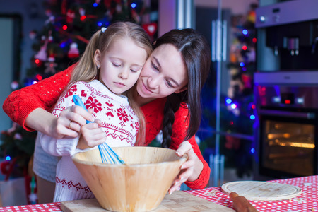 Little girl with young mother baking Christmas gingerbread cookies together photo